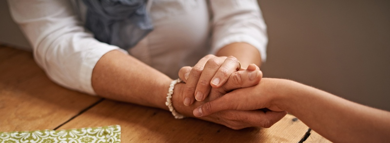 woman holding a loved one's hand in support